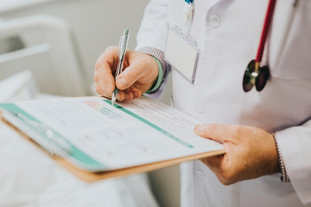 doctor writes on a clipboard