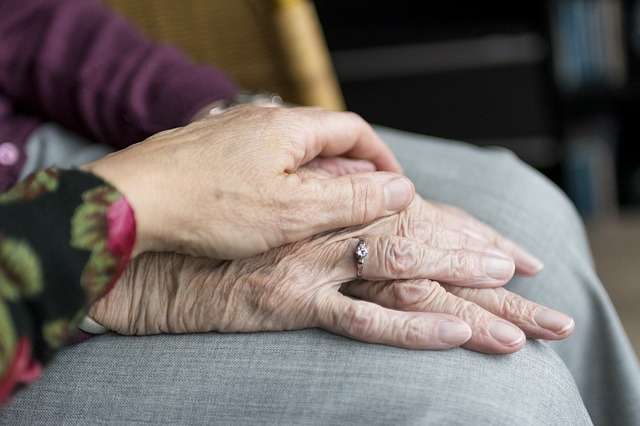 a hand comforts an older person