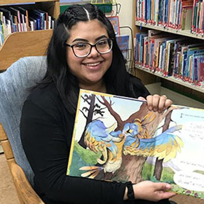 Librarian holding up a picture book and smiling
